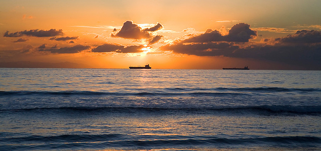 A cargo ship sails near Long Beach Harbor during sunset.