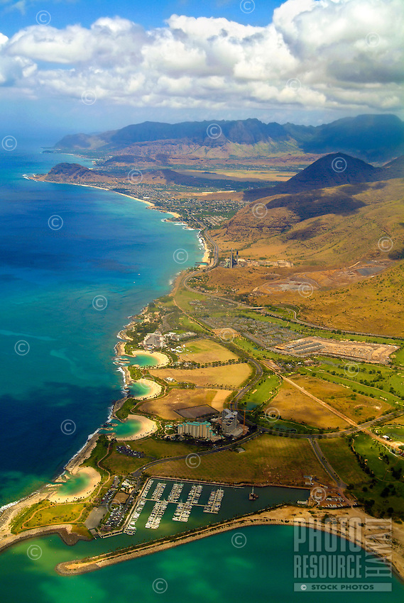 Aerial of the four crescent beaches and lagoons, Ihilani resort, golf course, and boat marina at Ko Olina along the Leeward (Western) Coast of Oahu. Beyond, along Farrington Highway, is the Kahe power plant and Electric Beach, the community of Nanak