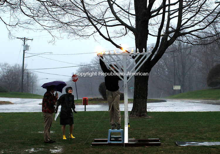 Middlebury, CT- 01, December 2010-120110CM02 Robert Rafford, the Middlebury Town Historian lights the Menorah Wednesday afternoon on the Middlebury Green. Several locals, including, Rachel Bashevkin, Director of Studies at the Westover (left) endured the rain storm to celebrate the beginning of Hanukah, which started yesterday (Wed.)     Christopher Massa Republican-American