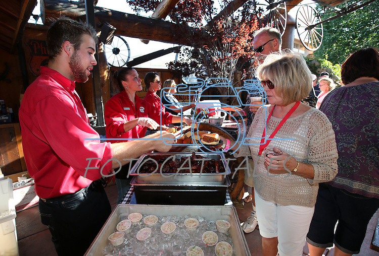 Austin Pacheco serves Judy Kassemos at Red's Old 395 during the 20th annual Taste of Downtown event in Carson City, Nev., on Saturday, June 15, 2013. The event features 44 local restaurants in a fundraiser for the Advocates to End Domestic Violence.<br /> Photo by Cathleen Allison