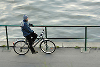 Poland, Krakow, Man on bicycle, resting on railing at riverside