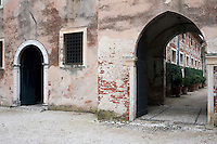 An arch in the distressed plaster wall of the stable block leads into an inner courtyard