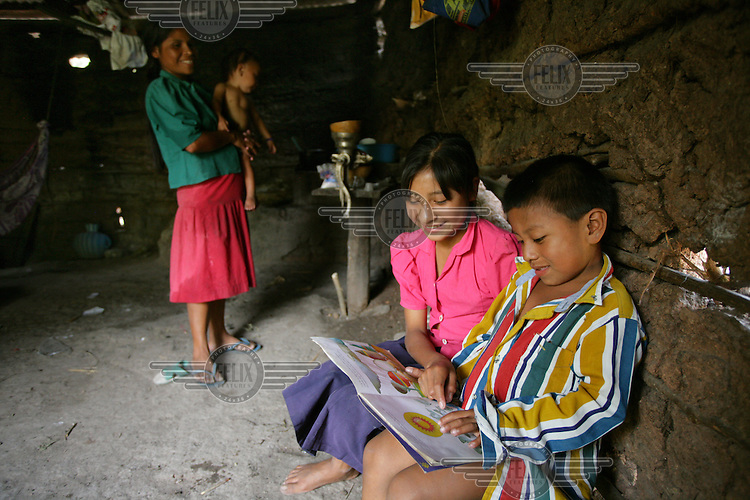 Children reading in their home, with mother and baby in background, in the Maya Chorti (Ch'orti) indigenous community of Nueva San Isidro.