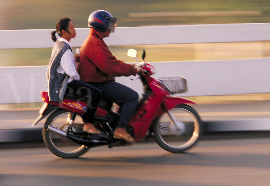 Man and woman on motorscooter driving on road. Panned background. Chiang Mai, Thailand.