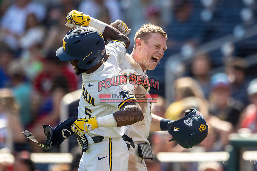 Michigan Wolverines first baseman Jimmy Kerr (15) and outfielder Christian Bullock (5) celebrate Kerr's home run against the Texas Tech Red Raiders in the 7th inning of the NCAA College World Series on June 21, 2019 at TD Ameritrade Park in Omaha, Nebraska. Michigan defeated Texas Tech 15-3 and will play in the CWS Finals. (Andrew Woolley/Four Seam Images)