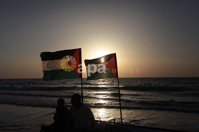 Palestinian men sit on a boat during the sunset on a beach in Gaza City May 2, 2014. Photo by Ashraf Amra