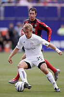 The New England Revolution's Taylor Twellman plays the ball in front of Mark Lisi of the MetroStars. The MetroStars and the New England Revolution played to a 2 - 2 tie at Giant's Stadium, East Rutherford, NJ, on Saturday May 21, 2005. Twellman scored both of New England's goals.