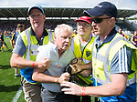 A Clare fan is removed by stewards after he invades the pitch following their All-Ireland quarter final against Wexford at Pairc Ui Chaoimh. Photograph by John Kelly.