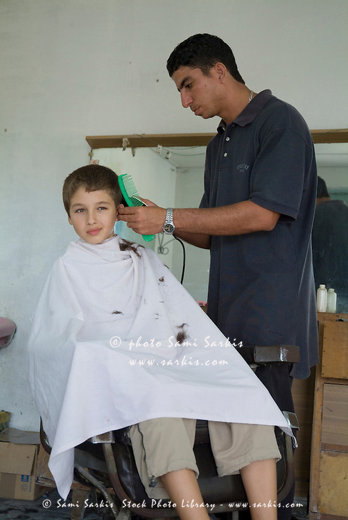 Boy receiving a haircut at a barbershop in Vinales, Pinar del Rio Province, Cuba.