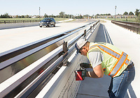 NWA Democrat-Gazette/CHARLIE KAIJO George Goodman of Emery Sapp and Sons applies primer to the bolts of a pedestrian railing, Monday, October 7, 2019 at the Magnolia St. overpass in Rogers.