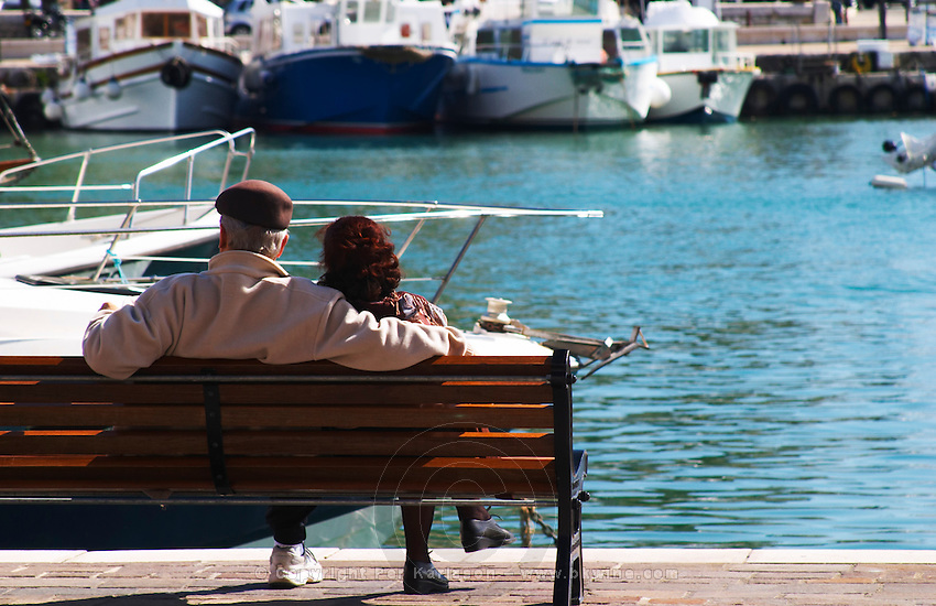 In the harbour in Cassis village. Fishing and leisure boats moored at the key side. A romantic couple man and woman sitting on a bench looking out over the boats. Cassis Cote d'Azur Var France Bouches du Rhone