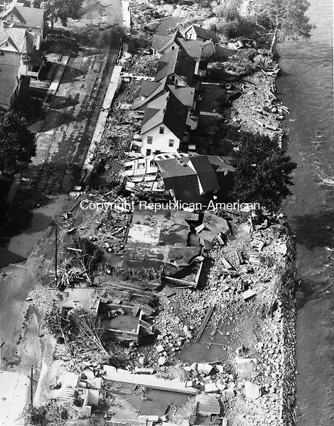 An aerial view of Naugatuck from August 20th 1955. This image shows the effects of flood waters after they whirled through the area in the wake of the heaviest recorded rainfall in New England annals. Most of the dwellings in center were moved off their foundations and tilted at crazy angles.
