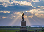 Gettysburg National Military Park, PA<br /> Evening sun rays breaking thru clouds over the monument to the 72nd PA Infantry