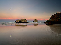 Moonset over Cannon Beach at low tide. Oregon
