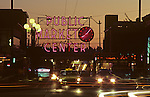 Sunset at the Pike Place Market with neon signs and clock illuminated with traffic car light streaks Seattle, Washington State USA