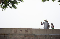 An elderly Chinese talks to a girl on the ancient Qingming Bridge over the Grand Canal of China in Wuxi, Jiangsu province, in June, 2014.