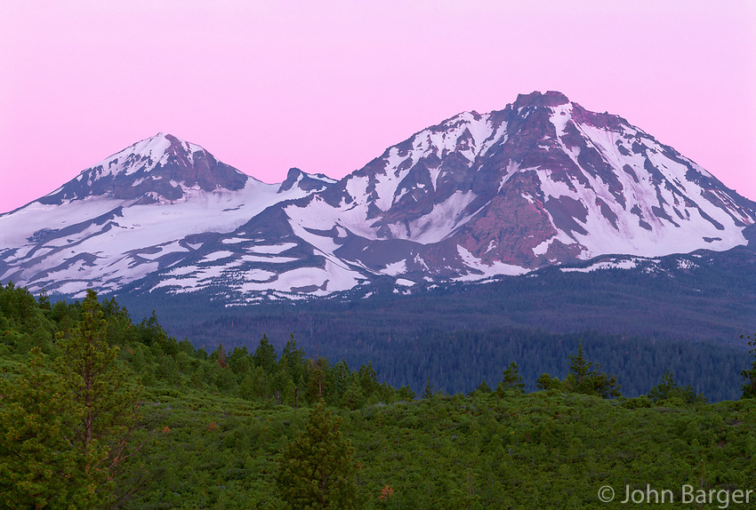 USA, Oregon, Deschutes National Forest, Pink sky at dawn sky Middle Sister (left) and North Sister (right) in the Three Sisters Wilderness