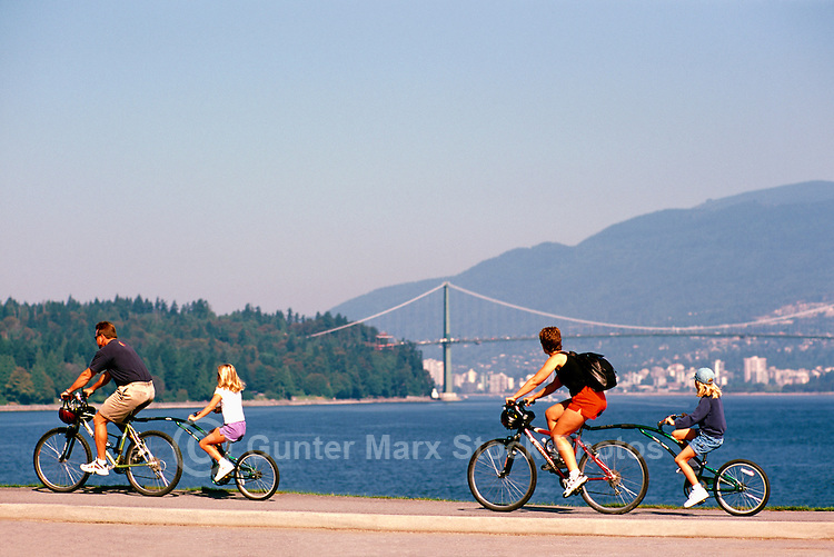 Stanley Park, Vancouver, BC, British Columbia, Canada - Family cycling on Tandem Bikes on Seawall along Burrard Inlet in Summer - Lions Gate Bridge, West Vancouver, and North Shore Mountains in background