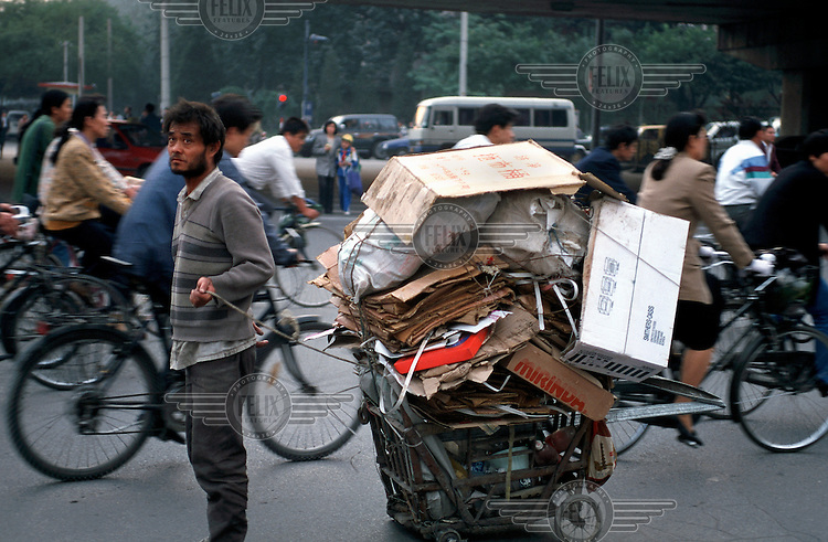 Migrant with cardboard collected to sell for recycling.
