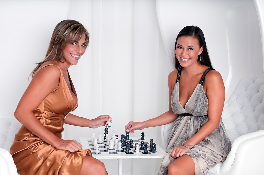 Young woman playing chess with night dress in upscale location.