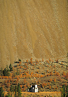 old wooden church is dwarfed by hillside of scree. Fall colors, erosion, cliff, mountain, rock, rubble, danger, landslide, religion. Cache Creek British Columbia Canada Cariboo.