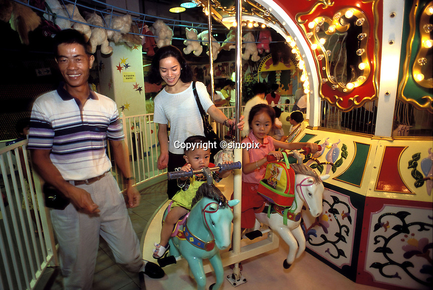 Parents and children ride a merry-go-round at an amusement park in Guangzhou, China.