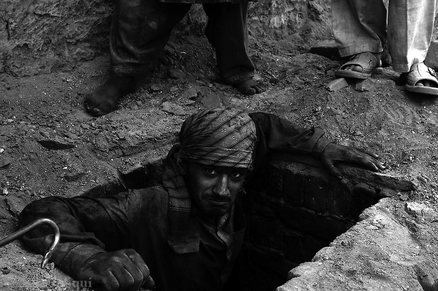 A worker steps down into a pit to check the condition of the baked bricks.  before the pit if fully exposed and the baked bricks removed, men go down these pits to check the condition of the bricks.  jalozai, peshawar, pakistan.  september 2003&amp;#xA;&amp;#xA;copyright asim rafiqui 2003<br />