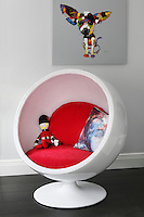 A toy soldier sits happily on the bright red cushions in the retro egg chair in the playroom