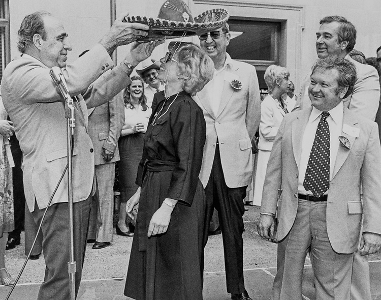 Rep. Henry B. Gonzalez, D-Tex. putting the crowned hat on a woman. (Photo by CQ Roll Call)