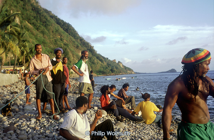 Villagers wait on the beach with one end of a seine net as fishermen attempt to catch tuna feeding close to shore at Pointe Michel.