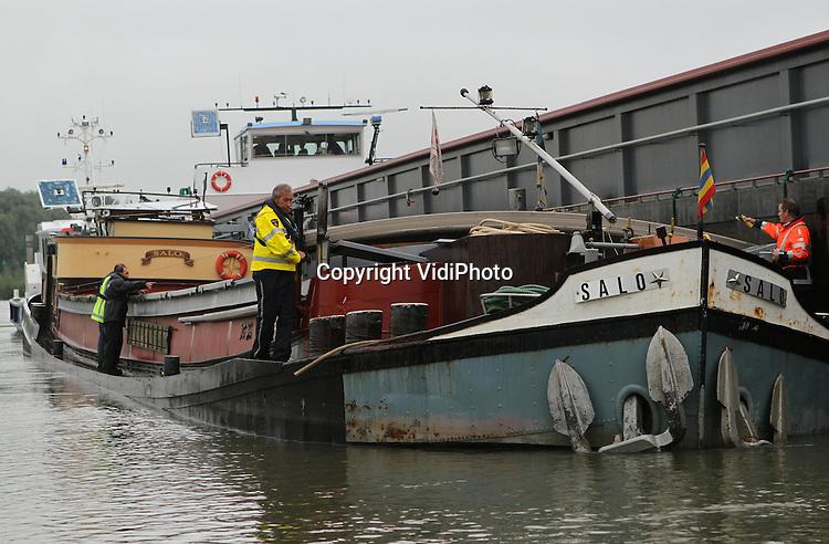 Foto: VidiPhoto..LEUVENHEIM - Een aanvaring op de IJssel tussen twee vrachtschepen, ter hoogte van Leuvenheim, heeft donderdag het leven gekost van de schipper van de kleinste boot. Zijn vijftig meter lange schip, de Salo, botste door nog onbekende oorzaak op de 110 meter lange Vlieland. Vermoedelijk is hierdoor het stuurhuis van de eerste boot ingestort. Naar verluidt is de schipper hier nog zelf uitgekomen, maar is hij daarna op het dak ineengezakt. Politieagenten die snel ter plaatse waren zijn het water ingesprongen en naar de boot gezwommen om eerste hulp te verlenen. Reanimatiepogingen mochten niet meer baten. De waterpolitie van het KLPD is een onderzoek gestart naar de toedracht van het incident.