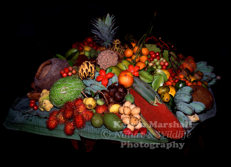 A large collection of edible exotic tropical fruit is displayed for tourists to observe.