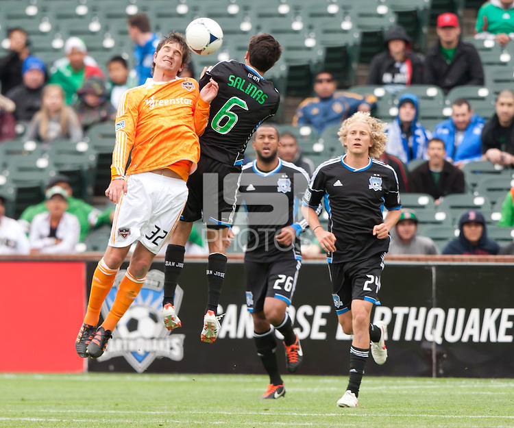 San Francisco, California - Saturday March 17, 2012: Bobby Boswell jumps for the ball against Shea Salinas during the MLS match at AT&T Park. Houston Dynamo defeated San Jose Earthquakes  1-0