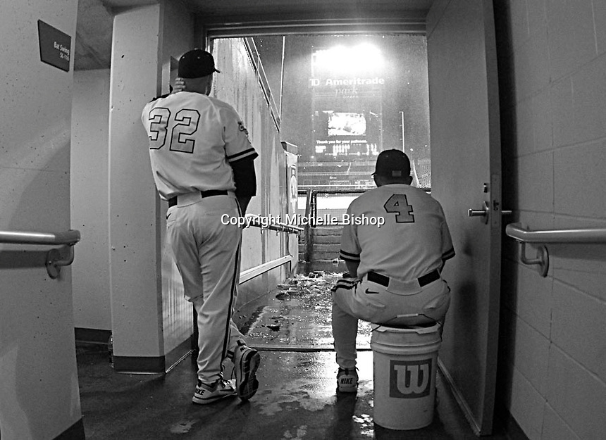 Vanderbilt Assistant Coach Josh Holliday (32) and Head Coach Tim Corbin (4) watch as rain pours onto the field at TD Ameritrade Park on June 20, 2011. The game between Vanderbilt and Florida was suspended in the sixth inning after a two-and-a-half hour delay. (Photo by Michelle Bishop)..