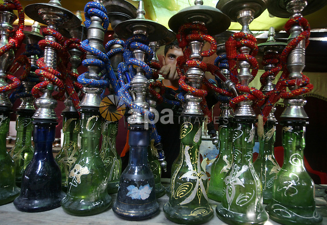 A Palestinian worker makes ready flavoured tobacco water pipes or 'shisha' prior to the evening influx of customers in Gaza City on July 17, 2010, as the ruling Islamic Hamas party tries to impose a ban on smoking water pipes in public. Photo by Ashraf Amra