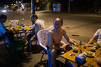Men drink beer and eat snacks such as garlic with green beans at a roadside restaurant near the west gate of the Ciqikou area of Shapingba district in Chongqing, China. Ciqikou's ancient town is a major tourist destination in Chongqing, but at night, the tourists disappear and locals come out to eat from street food vendors in the area.