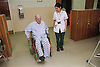 Female occupational therapist assessing elderly patient's mobility and independence by observing use of wheelchair,