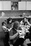 Chiswick Women's Aid, Richmond London Uk 1975. Jo Polaine, House mother feeding baby.