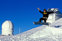 Man jumping in the air on a snowboard near the observatories on Mauna Kea, Big Island of Hawaii