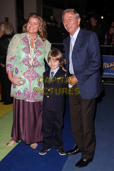 "DES O'CONNOR (R) & FAMILY.The Press Night for the new musical stage production of the ""Wizard of Oz"", London Palladium, London,.England, UK..March 1st, 2011.full length blue suit jacket son wife suit couple checked check paid trousers brown purple green tunic .CAP/AH.©Adam Houghton/Capital Pictures."