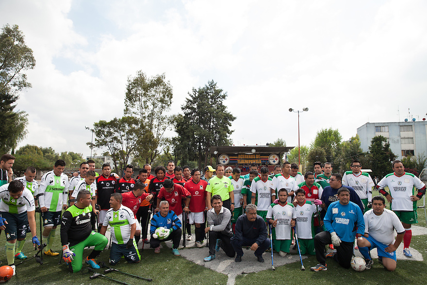 "Mexico Amputee Soccer tean's Guerreros Aztecas  (""Aztec Warriors"") and Los Dragones (""The Dragons"") pose for a pre-match photo in Deportivo Tlalli II in Talnepantla, Mexico on September 27, 2014. Guerreros Aztecas is Mexico City's first amputee football team. Founded in July 2013 by five volunteers, they now have 23 players, seven of them have made the national team's shortlist to represent Mexico at this year's Amputee Soccer World Cup in Sinaloa this December. The team trains twice a week for weekend games with other teams. No prostheses are used, so field players missing a lower extremity can only play using crutches. Those missing an upper extremity play as goalkeepers. The teams play six per side with unlimited substitutions. Each half lasts 25 minutes. The causes of the amputations range from accidents to medical interventions – none of which have stopped the Guerreros Aztecas from continuing to play. The players' age, backgrounds and professions cover the full sweep of Mexican society, and they are united by the will to keep their heads held high in a country where discrimination against the disabled remains widespread. (Photo by Bénédicte Desrus)"