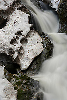 Patchesof snow hold on against the forthcoming spring at Thunderbird Falls near Chugiak, Alaska.