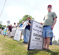 Protesters hold signs during an anti drone protest at the Horsham Drone Command Center Saturday June 25, 2016 at the old Willow Gove Naval Air Station in Horsham, Pennsylvania. (Photo by William Thomas Cain)