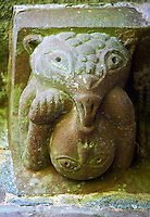 Norman Romanesque exterior corbel no 50  -  sculpture of.a curious scene. A beaked headed creature holds down a man below its body and is pushing its beak into the mans mouth, The beaked creature seems to be holding something in its right hand which it is eating The Norman Romanesque Church of St Mary and St David, Kilpeck Herefordshire, England. Built around 1140