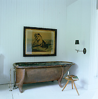 Situated against pristine white tongue-and-groove panelling the antique free-standing bath is the focal point of the bathroom; next to it is an old milking stool, an antique shop find