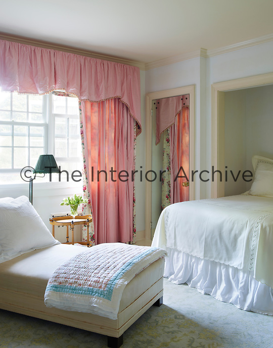A pretty white guest room is given a burst colour by the addition of pink curtains with a deep pelmet.
