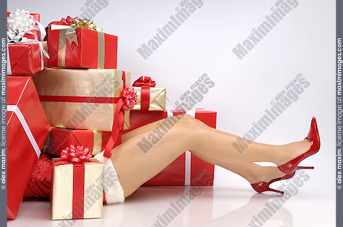Woman buried under Christmas gifts with only legs visible. Isolated on white background.