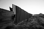 Agua Prieta, Mexico/Douglas, Arizona<br /> October 22, 2006<br /> <br /> Mexicans illegally scale the border fence to enter the United States.