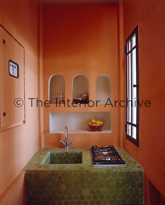 Colour brings this narrow kitchen to life - the bright orange walls contrasting with the green of the vitrified tiles of the sink unit
