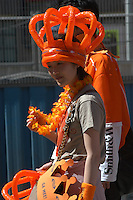 AMSTERDAM-HOLANDA-  Unas mujeres joven camina durante el día de la Reina con una corona color naranja./ A young woman walk during the Queen's day with a orange crown. Photo: VizzorImage/STR